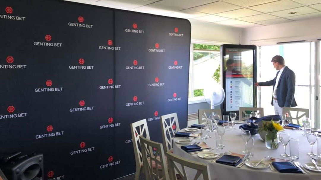 man interacting with digital screen at Windsor Racecourse